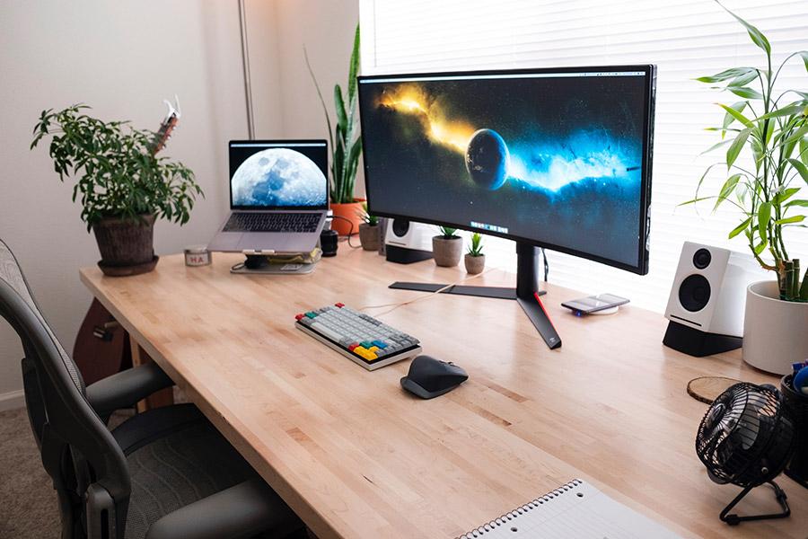 stand laptop pe birou langa monitor
